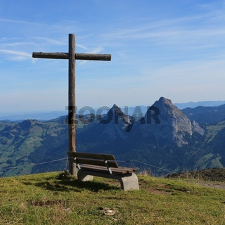 Summit cross and bench on the summit of Mount Fronalpstock, Switzerland.