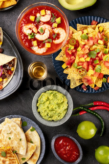 Mexican food, many dishes of the cuisine of Mexico, flatlay, top shot on a black background. Nachos, tequila, guacamole, shrimp cocktail, quesadillas