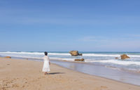 Girl in wedding dress running along the beach
