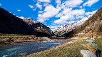 Mountain valley with stream, trees, small hut and dried Livigno lake, Alps, Italy