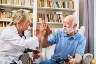 Ärztin und Senior Mann geben sich High Five