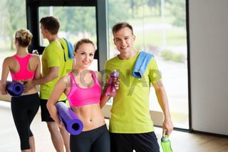 couple with bottles, exercise mat and towel in gym