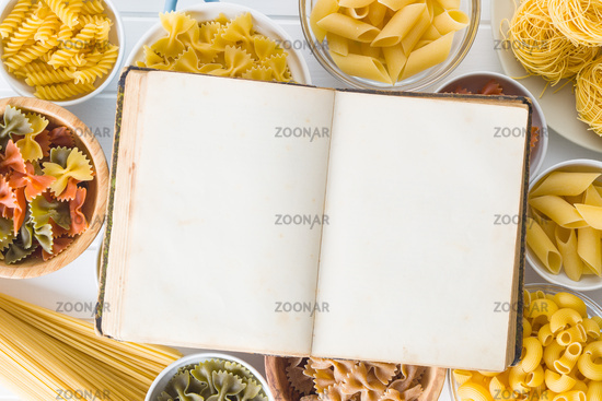 Various types of italian pasta and blank cookbook.