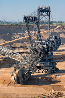 Brown coal open pit landscape with digging excavator in Germany