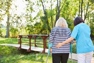 Krankenschwester unterstützt Seniorin beim Gehen