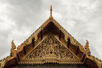 Decorative golden fresco under Grand Palace roof