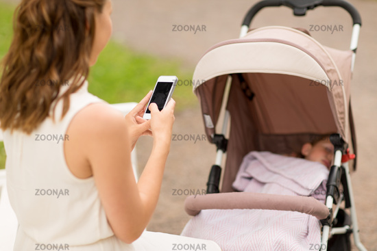 mother with smartphone and baby in stroller