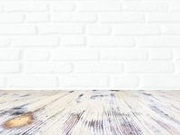 washed wood table with white brick wall texture background.