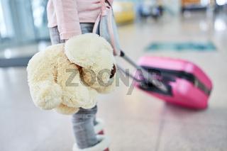Kind mit Kuscheltier im Flughafen Terminal