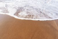 Soft sea Wave On Sandy Beach. Summer and vacations and travel concept. Selective focus, with copy space.