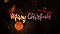 Merry Christmas text, candle and green tree branches on wood background