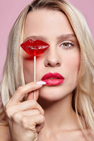 Portrait of blonde woman closing by candy her eye.. Red female lips shape lollipop. Sweet tooth concept