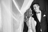 Groom hugs bride tenderly in the shadow of a flying veil.