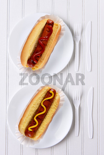 Top view of an all white place setting with hot dogs one with ketchup, one with mustard.