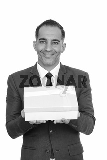 Mature happy Persian businessman giving gift box ready for Valentine's day