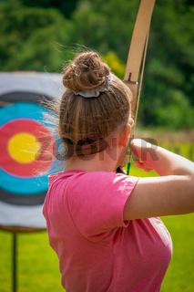 Ein übendes Bogenschießen der jungen Frau zielt auf ein Ziel mit einem Pfeil und Bogen auf einem Lan