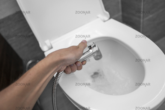Using of bidet shower with a white toilet. Bidet shower in male hand for using with a white toilet bowl.