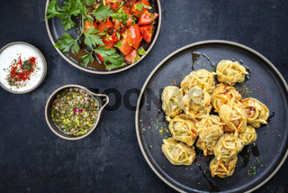Traditional Kazakh manti steamed with mincemeat and tomato salad as top view on a modern style plate