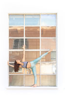 Fit sporty active girl in fashion sportswear doing yoga fitness exercise in front of gray wall, outdoor sports, urban style
