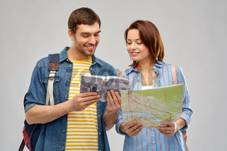happy couple of tourists with city guide and map