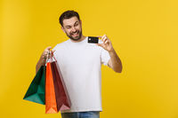 portrait of smiling couple holding shopping bags and credit card isolated on yellow background.