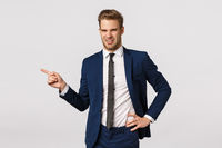 Eeew disgusting scene. Young male entrepreneur in classic suit, pointing left and grimacing with aversion, cringe from reek, bad smell, or unappealing person, standing reluctant white background