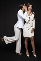 Stunning friends in white suits gossiping on black backgroud.