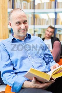 Mann als kompetenter Dozent mit einem Buch