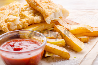 Traditional British street food fish and chips with ketchup sauce on parchment paper