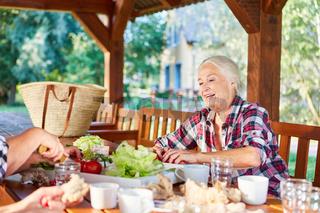 Senior Frau im Garten beim gesunden Frühstück