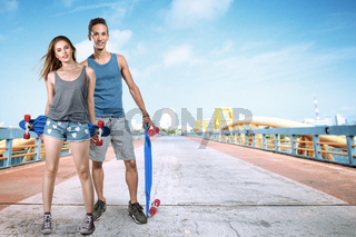 Young man and woman with skateboard posing on city street