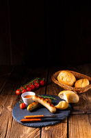 rustic bratwurst with ketchup and fresh rolls