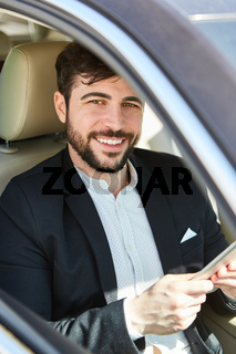 Business Mann im Auto mit Tablet Computer