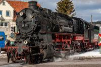 Dampflok 58311 verlässt Bahnhof und passiert Bahnübergang