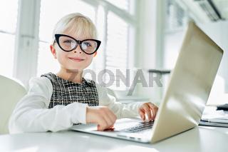 Mädchen als Geschäftsfrau vor Laptop Computer