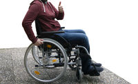 Man in wheelchair on washed concrete slab, thumbs up