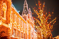 Illuminated GUM facade and New year festive decorations on Red Square, main landmark in Moscow. Christmas fair in Russia at evening while snow falling