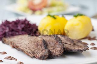 deutschen Sauerbraten mit Rotkohl auf einem Teller