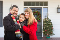 Young Mixed Family On Front Porch of House with Christmas Decorations