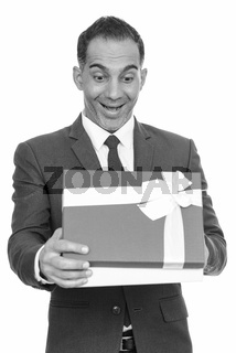 Mature happy Persian businessman opening gift box