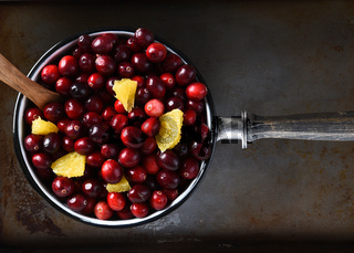 A pot full of fresh cranberries and orange pieces ready to be made into cranberry sauce a traditional Thanksgiving side dish.