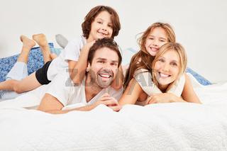 Familie mit zwei Kindern liegt auf dem Bett