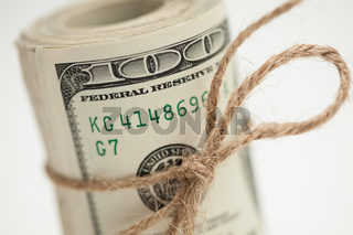 Roll of One Hundred Dollar Bills Tied in Burlap String on White