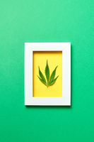 Creative yellow handmade frame with cannabis leaf on a green background.