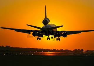 Takeoff of a passenger plane on the background of a sunset.