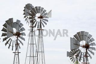 metal wind wheels under an overcast sky