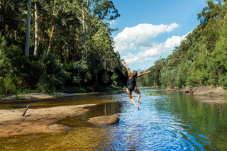 Active Aussie woman jumping into river remote bushland