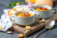 Pumpkin soup with bacon in a rustic style.