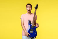 Handsome young musician playing the guitar and singing, isolated on yellow background