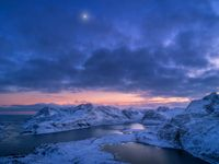 Aerial view of snowy mountains, sea, colorful cloudy sky at night